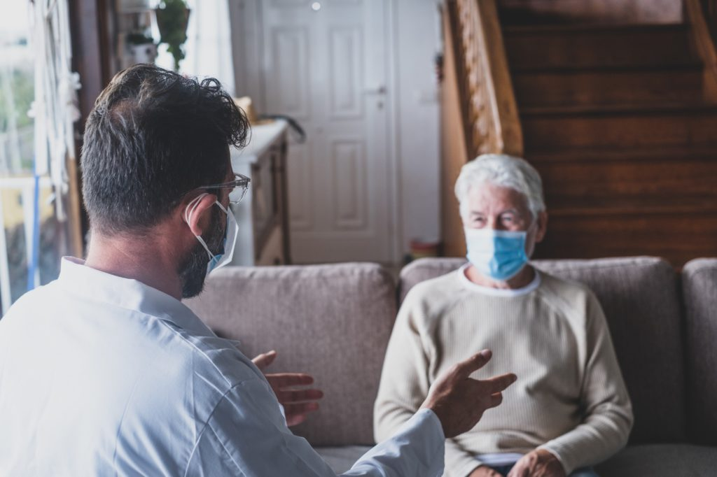 Male professional doctor consulting senior patient during medical care visit wearing masks.