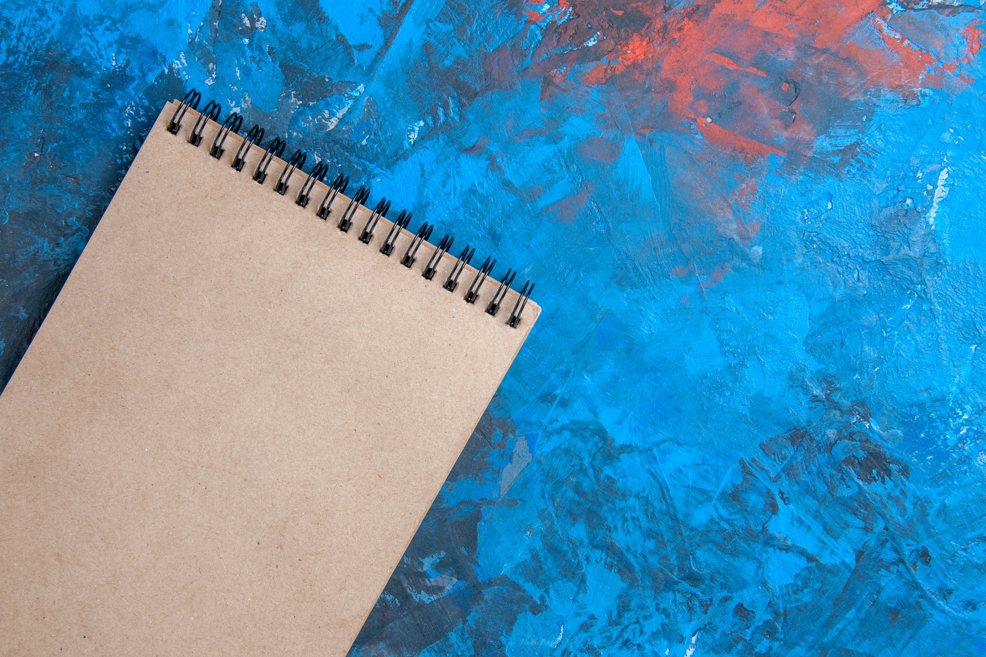 top close view a notebook on blue background free space